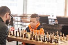 Jongen het spelen schaak met vader op de toernooien van een familieschaak op een school stock afbeeldingen