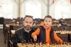 Jongen het spelen schaak met vader op de toernooien van een familieschaak op een school stock fotografie