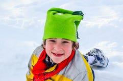 Jongen het Spelen in Sneeuw met Groene Hoed stock fotografie