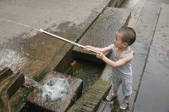 Jongen het spelen waterkanon Stock Afbeeldingen