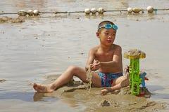 Jongen het spelen zand in de zomerstrand Royalty-vrije Stock Foto's