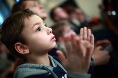 Jongen het toejuichen in theater Stock Afbeeldingen