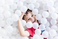 Jongen het verbergen onder witte ballen bij de speelplaats royalty-vrije stock afbeeldingen