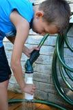 Jongen het vullen container met buiten het water geven van slang Stock Foto's
