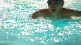 Jongen het zwemmen vlinderslag in de pool stock footage