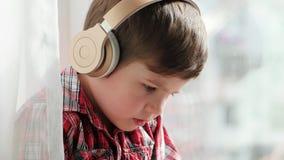 Jongen in hoofdtelefoons met smartphone, close-upportret weinig jong geitje die overhemd het letten op beeldverhalen dragen stock videobeelden