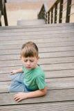 Jongen 5 jaar ols zittings op een ladder met dichte ogen royalty-vrije stock foto