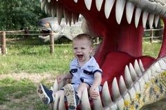 Jongen in kaken van dinosaurus stock afbeelding