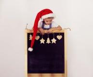 Jongen in Kerstman` s hoed met verfraaid bord stock afbeelding