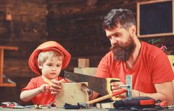 Jongen, kind bezig in beschermende helm die handsaw met papa leren te gebruiken Vader, ouder die met baard weinig zoon onderwijze royalty-vrije stock foto's