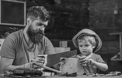 Jongen, kind bezig in beschermende helm die handsaw met papa leren te gebruiken Vader, ouder die met baard weinig zoon onderwijze royalty-vrije stock fotografie