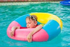 Jongen in kleurrijke vlotterring in zwembad royalty-vrije stock fotografie