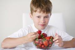 Jongen met aardbeien Stock Afbeelding
