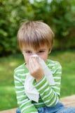 Jongen met allergie die zijn neus behandelen royalty-vrije stock afbeelding