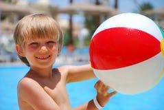 Jongen met bal bij pool royalty-vrije stock afbeeldingen
