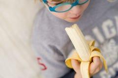 Jongen met banaan - kind dat banaan eet royalty-vrije stock afbeelding