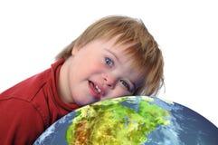 Jongen met benedensyndroom en aarde Stock Fotografie