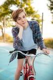 Jongen met blond haar in borrels en toevallig overhemd die zich met rode fiets op basketbalhof bevinden in park Jonge mens dreami stock afbeelding