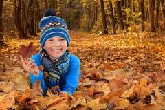 Jongen met de bladeren van de Herfst Royalty-vrije Stock Afbeelding