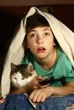Jongen met de verschrikkingsfilm van het kattenhorloge Stock Fotografie