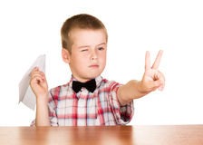 Jongen met document vliegtuigzitting bij een lijst op wit wordt geïsoleerd dat stock afbeelding