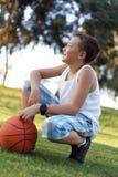 Jongen met een bal in de verse lucht in het park Stock Foto's