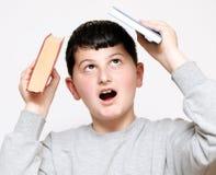 Jongen met een boek op zijn hoofd Stock Afbeeldingen