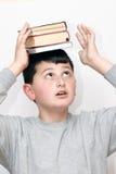 Jongen met een boek op zijn hoofd stock afbeelding