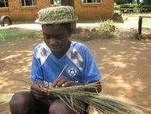 Jongen met een grashoed die een hoed van gras weven Stock Afbeeldingen