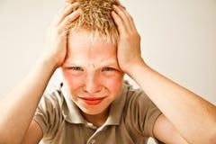 Jongen met een hoofdpijn Stock Afbeeldingen