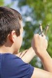 Jongen met een katapultdoel aan de boom Royalty-vrije Stock Afbeeldingen