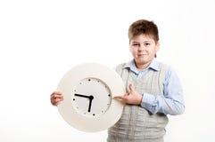 Jongen met een klok op een lichte achtergrond Stock Fotografie