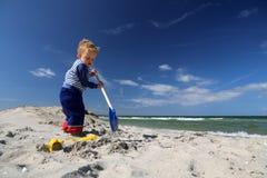 Jongen met een schop bij het strand Stock Afbeelding