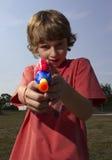 Jongen met een stuk speelgoed kanon Stock Afbeelding