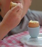 Jongen met ei voor ontbijt Stock Fotografie