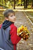 Jongen met esdoornbladeren Stock Foto