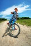 Jongen met fiets op een landweg door weide Royalty-vrije Stock Foto