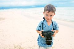 Jongen met fotocamera op strandachtergrond stock afbeelding