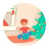 Jongen met gift Kerstmis of nieuw jaar Dichtbij de verfraaide boom en de open haard Royalty-vrije Stock Afbeelding