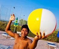 Jongen met groene en gele kostuumtreinen met de bal om v te spelen Royalty-vrije Stock Afbeeldingen