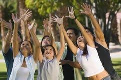 Jongen (13-15) met groep jonge volwassenen die naar omhoog bereiken. Stock Fotografie