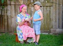 Jongen met Grootmoederholding Jong Chick Outdoors stock afbeelding