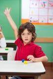 Jongen met Hand Opgeheven Zitting bij Bureau stock afbeeldingen
