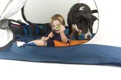 Jongen met het magnifiying van glas en hond het tenting Stock Afbeelding