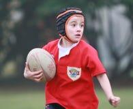 Jongen met het rode rugby van het jasjespel Royalty-vrije Stock Foto