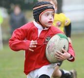 Jongen met het rode rugby van het jasjespel Stock Afbeeldingen