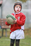 Jongen met het rode rugby van het jasjespel Royalty-vrije Stock Afbeelding