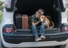 Jongen met hond en koffers in de boomstam van een auto Stock Fotografie