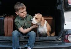 Jongen met hond en koffers in de boomstam van een auto Royalty-vrije Stock Fotografie