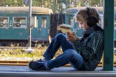 Jongen met hoofdtelefoon en gitaar stock afbeelding